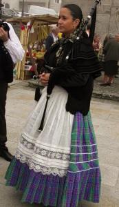 Soort doedelzakspeelster die voor de processie loopt